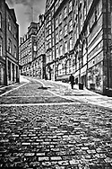 Briefcase in hand, the man walks home from work on an isolated street in Newcastlel-on-Tyne, England.  Aspect Ratio 1w x 1.5h.