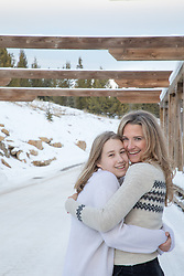 mom and her daughter hugging outdoors