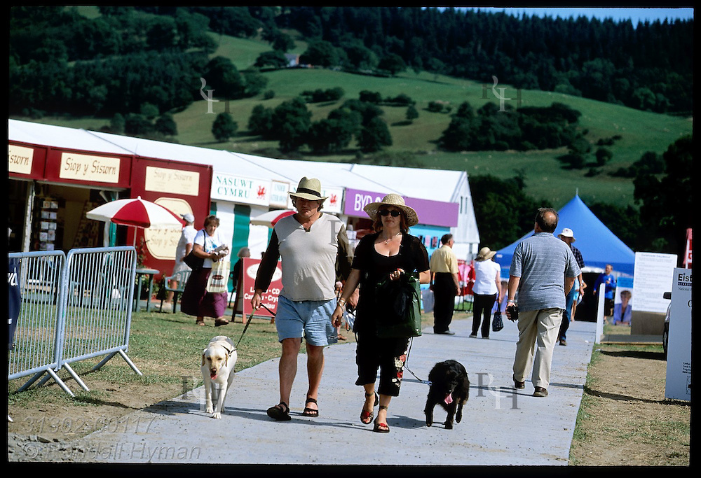 Couple walks dogs past booths showcasing Welsh culture at fairgrounds of the annual National Eisteddfod festival; Meifod, Wales.
