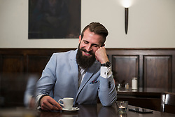 Well-dressed man looking at coffee cup and thinking while sitting at restaurant