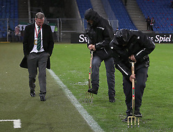 Northern Ireland manager Michael O'Neill walks past ground staff using pitchforks to help drain the rainwater from the pitch before the FIFA World Cup Qualifying second leg match at St Jakob Park, Basel.