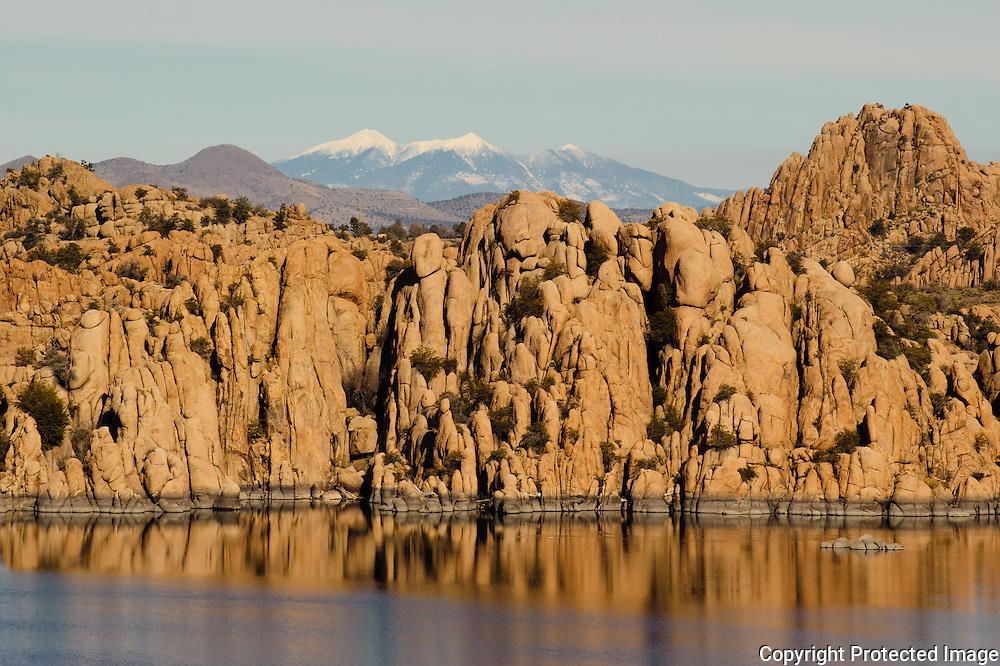The snow-capped San Francisco Peaks peak over the rocks at Granite Dells near Prescott, Arizona.