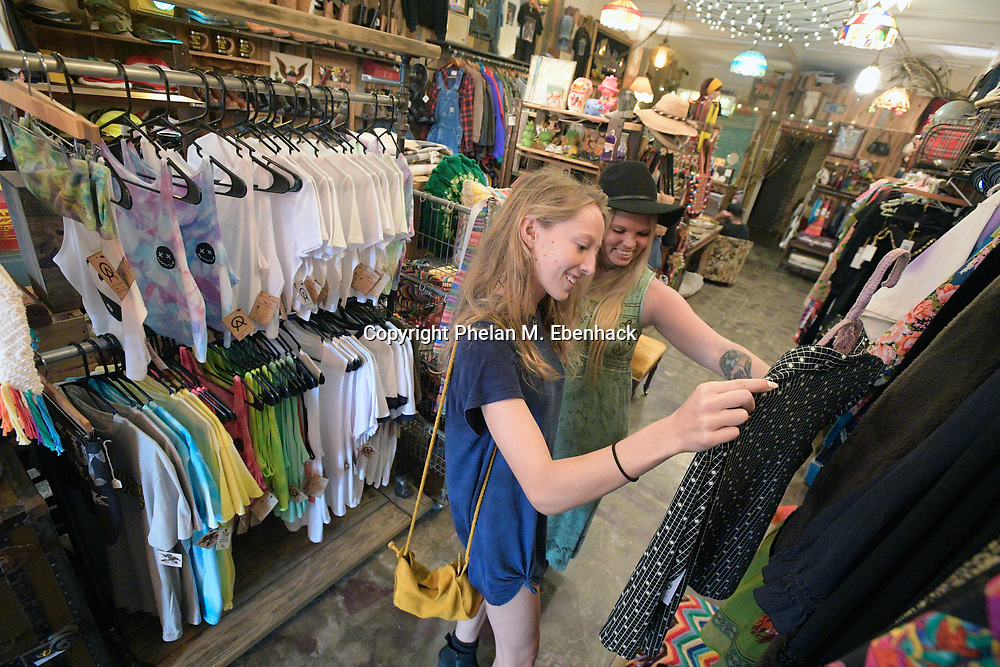 Brittany Sulser, right, owner of The Owl's Attic vintage store, helps Carson Brace look through some outfits in the Audubon Park neighborhood Saturday, Sept. 23, 2017, in Orlando, Fla. (Photo by Phelan M. Ebenhack)