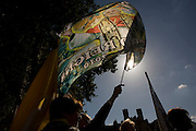 British Papal supporters wave flags during Pope Benedict XVI's papal tour of Britain 2010, the first visit by a pontiff since 1982. Taxpayers footed the £10m bill for non-religious elements, which largely angered a nation still reeling from the financial crisis. Pope Benedict XVI is the head of the biggest Christian denomination in the world, some one billion Roman Catholics, or one in six people. In Britain there are about five million Catholics but only a quarter of Catholics regularly attend Sunday Mass and some churches have closed owing to spending cuts.
