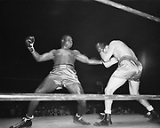 """Y-480302-1.This photo, titled """"Haymaker Coming Up,"""" won first place in the 1948 Associated Press annual photography awards in the sports category. Bobby Zander, of Los Angeles, tosses a haymaker at Joe Kahut before a sellout crowd of 4700, with 3000 turned away, at Portland's Civic Auditorium on March 2, 1948. In the 4th round Kahut began to land left hand blows to Zander's body, followed up by rights to the head, while Zander responded with headshots of his own, while doubling up Kahut with a blow to the mid-section. Thirty seconds into the fifth round, a left hook to the jaw from Kahut floored Zander for the ten-count."""