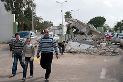 © under license to London News Pictures. 24/02/2011. A family walks by the entrance to the destroyed Army compound in the Libyan city of Benghazi. Photo credit should read Michael Graae/London News Pictures