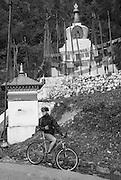 MTN BIKING, BHUTAN. A cyclist (Mike), pauses beside a no name Buddhist chorten (stupa), and prayer flags beside the main road between  the Dochu La (pass) to the Punaka valley.