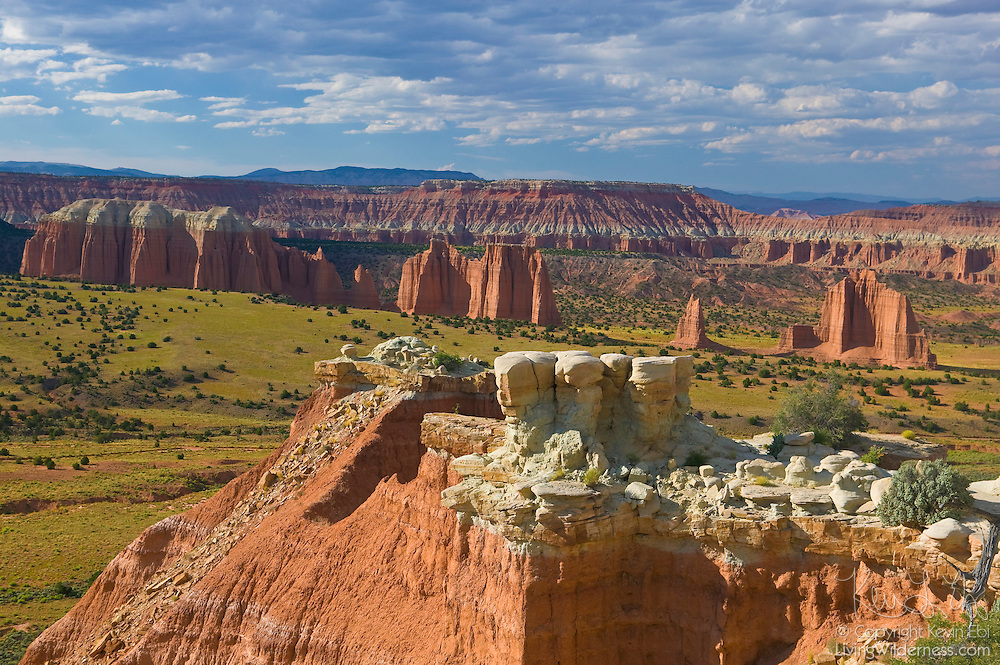 Several monoliths that make up the Cathedral Valley of Capitol Reef National Park, Utah, are visible from the summit of one of the peaks that lines the valley. The monoliths are carved from Entrada sandstone. Some peaks are capped with gray marine sandstone, known as the Curtis Formation.