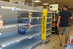 © Licensed to London News Pictures. 22/07/2021. London, UK. A man walks past nearly empty shelves of drinking bottled water in Tesco Express in Tottenham, north London after food shortage fears due to the pingdemic. A number of supermarkets are reporting empty shelves as they, wholesalers and hauliers are struggling to ensure food and fuel supplies after the Covid-19 NHS app alerted workers to isolate after being in contact with someone with COVID-19. Photo credit: Dinendra Haria/LNP