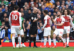 Refreee Anthony Taylor surrounded by Arsenal players, left to right<br /> Mesut Ozil, Lucas Torreira Shkodran Mustafi and Matteo Guendouzi