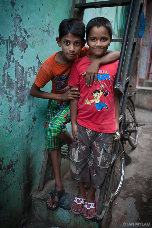 Two young friends stand together on a ladder in the Dharavi Slum, Mumbai, India