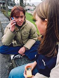 Teenage girls using mobile phone UK