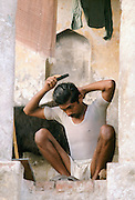 Indian man combing his hair and grooming himself at home