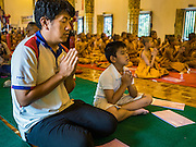 03 APRIL 2016 - CHIANG MAI, THAILAND: A man and his son participate in a meditation and prayer ceremony at Wat Chedi Luang in Chiang Mai. The meditation ceremony was in honor of the birthday of Her Royal Highness Princess Maha Chakri Sirindhorn, the daughter of Bhumibol Adulyadej, the King of Thailand. The Princess was born on April 2, 1955. She is revered by Thais and special ceremonies in her honor are held in temples throughout Thailand.     PHOTO BY JACK KURTZ