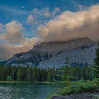 The moon sets over Cascade Mountain as the day breaks over Two Jack Lake in Banff National Park, Alberta, Canada.