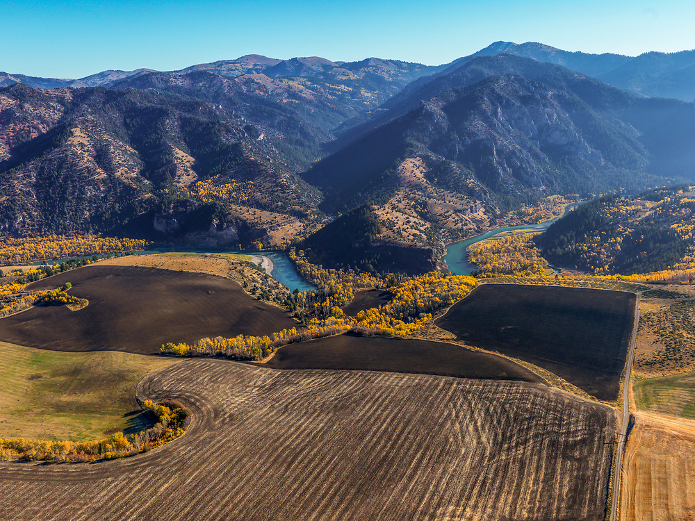 Aerial view of the South Fork of the Snake River up river from the town of Ririe in Eastern Idaho with agriculture land patterns and autumn colors
