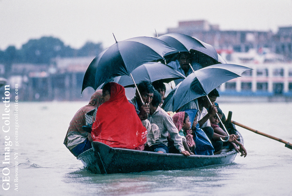 """Some 10,000 people crowd 12 at a time into the little wooden """"shawl Noka"""" boats to come to work in a downpour.  They pay 1/2 a Taka one way."""