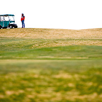 041813       Brian Leddy<br /> A spectator watches his son play golf in Grants Thursday at Coyote del Malpais Golf Course. Cold temperatures and heavy winds made the round challenging for many players.