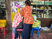 """17 FEBRUARY 2015 - BANGKOK, THAILAND: A woman works on a client at a threading stand on Charoen Krung Road in Bangkok's Chinatown. About a dozen people, mostly women, have set up shop on the sidewalk to do hair removal for clients. They use thread to remove hair, a practice called """"threading"""" which originated in India more than 6,000 years ago. It's growing in popularity in the US and Europe as an alternative to waxing. A cotton or polyester thread is pulled along unwanted hair in a twisting motion, the hair is trapped in a mini lasso, and lifted out of the follicle.    PHOTO BY JACK KURTZ"""