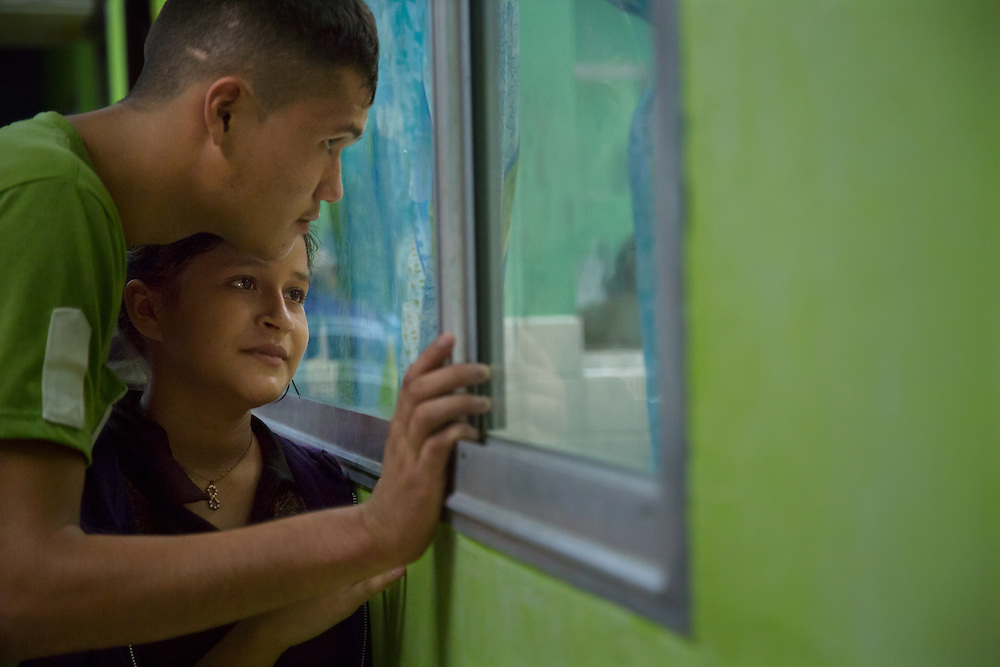 Teenage parents Daylin, 15, and Rubin, 17, observe their premature newborn at Hospital San Benito.