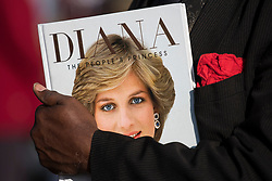 © Licensed to London News Pictures. 31/08/2017. London, UK. A man holds a book showing the face of Princess DIana, at the gates to Kensington Palace in London on the 20th anniversary of the death of Diana, Princess of Wales. Princess Diana was fatally injured in a car crash along with her companion Dodi Fayed, while the couple were being driven through the Pont de l'Alma tunnel in Paris on 31 August 1997. Photo credit: Ben Cawthra/LNP
