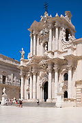 Tourists visiting Duomo di Siracusa cathedral Temple of Minerva - Tempio di Minerva - front elevation in Piazza Duomo in Ortigia, Sicily, Italy