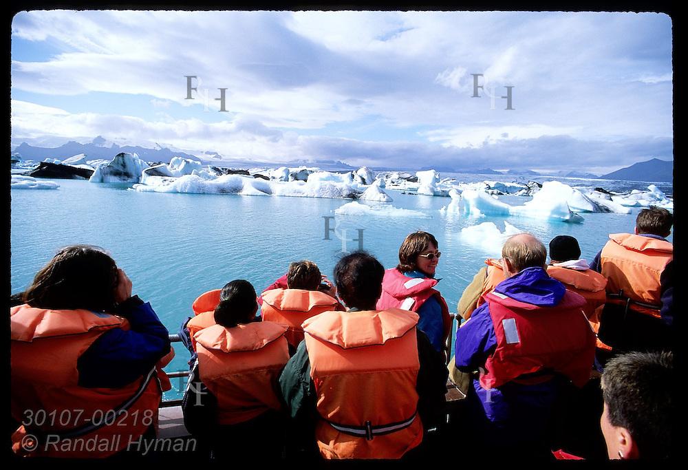 Tourists crowd one side of tour boat admiring ice calved from Breidamerkurjokull glacier in Glacier Lagoon (Jokulsarlon); SE Iceland.