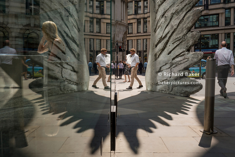 Londoners walk past the sculpture entitled City Wing on Threadneedle Street in the City of London, the capital's financial district, on 24th July 2018, in London, England. City Wing is by the artist Christopher Le Brun. The ten-metre-tall bronze sculpture is by President of the Royal Academy of Arts, Christopher Le Brun, commissioned by Hammerson in 2009. It is called 'The City Wing' and has been cast by Morris Singer Art Founders, reputedly the oldest fine art foundry in the world.