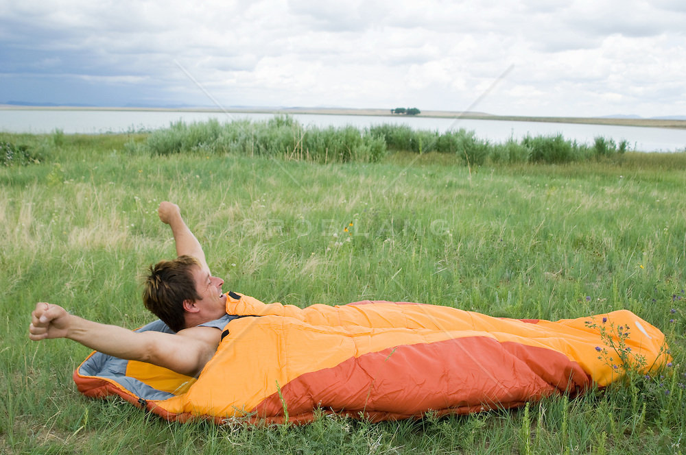 Man stretching as he wakes up in his sleeping bag in a grass area beside a lake in New Mexico
