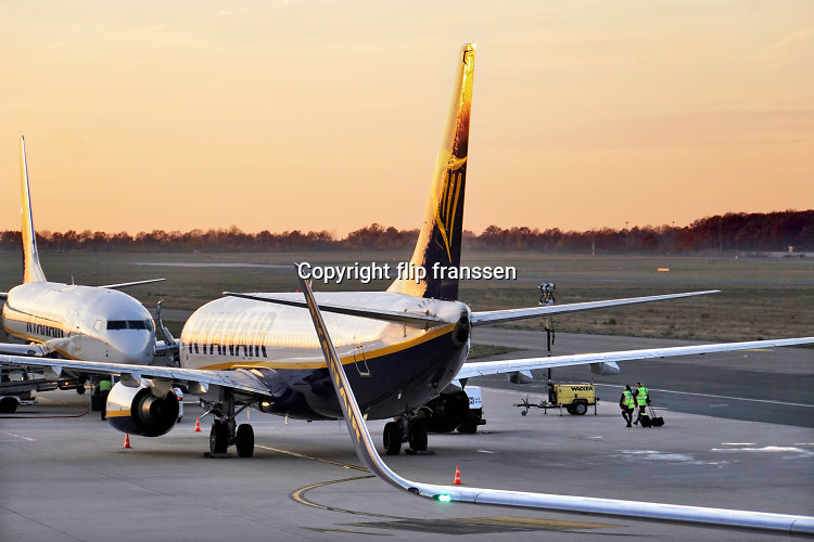 Duitsland, germany,deutschland, Weeze, 14-11-2018 Vlak over de grens van nederland ligt het regionaal vliegveld Niederrhein, Weeze, wat in tien jaar uitgegroeid is tot een belangrijke regionale luchthaven en als thuisbasis fungeert voor prijsvechter, chartermaatschappij Ryanair. Een crew, bemanning, loopt naar een van de toestellen voor een vlucht naar Valencia. In de regio bevindt zich ook vliegveld Dusseldorf. Naast passagiersvervoer wordt er veel luchtvracht vervoerd. Veel nederlanders uit oost gelderland, en noord limburg vliegen vanaf hier. Foto: Flip Franssen