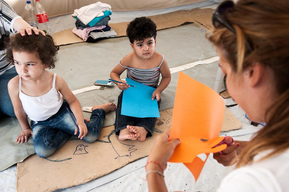 Sham 3yo and Bisan 2yo doing a programme with MSF psychiatrist Lena Zachou at her tent in Kara Tepe camp, Lesvos, Greece