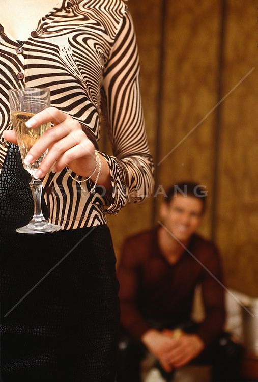 Man seated in background smiling while a woman holds a champagne glass in the foreground