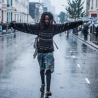 London, UK - 25 August 2014: a man walks under heavy rain during the Notting Hill Carnival in London.