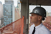 Investigative Engineering Services, Assistant Commissioner Tim Lynch inspecting a new construction site in Manhattan, New York City. Looking out to the NYC skyline, Tim works in the prevention of damage to old and ensuring new buildings are up to standard plus often, assessing the status of a collapsed structure. From the chapter entitled 'The Skyline' and from the book 'Risk Wise: Nine Everyday Adventures' by Polly Morland (Allianz, The School of Life, Profile Books, 2015).