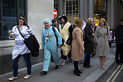 City workers in fancy dress for their Christmas party walk towards Bank. In all sorts of costumes, they are in happy mood having fun looking ridiculous. London, UK.