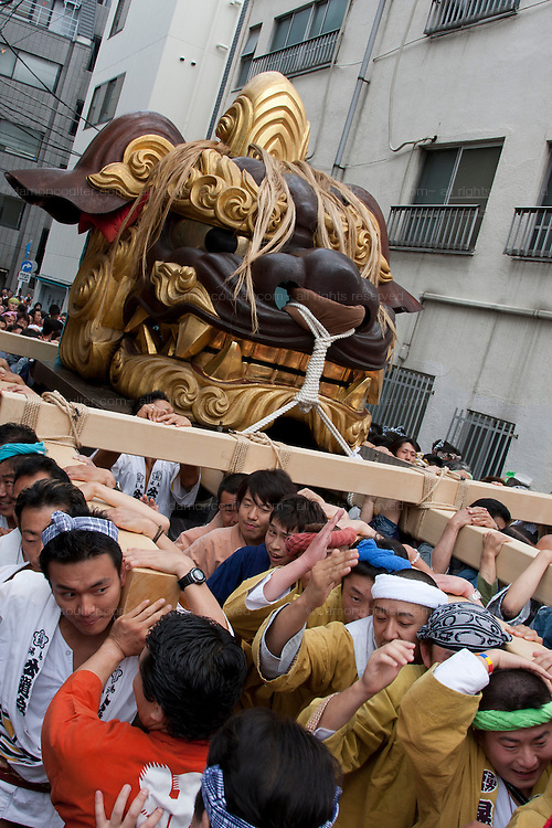 The Tsukiji Jishi or Shishi matsuri where large lion heads are carried around the streets. Tsukiji, Tokyo, Japan. June 14th 2009