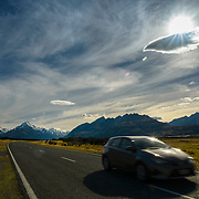 Car driving through mountain range on highway 80 towards Aoraki Mount Cook
