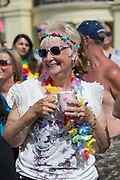 An elderly lady wearing rainbow garlands during the Brighton Pride parade and carnival on the 4th August 2018 at Hove Lawns in the United Kingdom. Brighton Pride is an annual event held in the city of Brighton and Hove, England, organised by Brighton Pride, a community interest company who promote equality and diversity, and advance education to eliminate discrimination against the lesbian, gay, bisexual and transgender community.