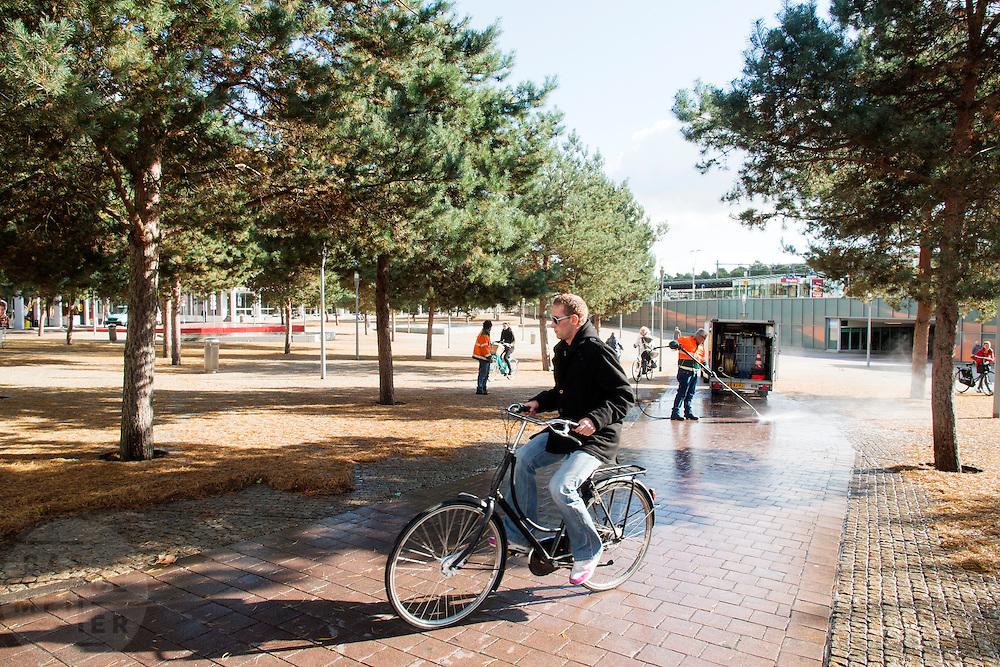 Een man op een fiets moet voor het station van Apeldoorn uitwijken omdat het fietspad wordt gereinigd.<br /> <br /> A man on a bicycle has to make a detour because the bike path in front of Apeldoorn station is cleaned.
