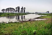Nederland, the Netherlands, Brummen, 10-5-2019 Het landschap tussen Voorst en Cortenoever, vlakbij Zutphen, is een gebied dat door de IJssel is gevormd. Met uitgestrekte uiterwaarden, stroomruggen en een aantal scherpe rivierbochten. Om het gebied langs de IJssel te beschermen tegen hoogwater zijn op twee plekken dijken landinwaarts verlegd. Zo is er meer ruimte voor de rivier wanneer het nodig is. Bij het verhogen van de waterveiligheid is op een slimme manier gebruik gemaakt van bestaande dijken in het gebied. Die zijn op strategische locaties – in het noorden en zuiden – verlaagd. Bovendien hebben de drempels verschillende hoogten. Daardoor stromen de uiterwaarden bij hoogwater gecontroleerd mee met de rivier en blijft de stroomsnelheid beperkt. Zo treedt er minder schade op. Als de waterstand in de IJssel weer zakt, zakt ook de waterstand in de overstroombare gebieden. Nieuw aangelegde gemalen pompen dan het laatste water uit het gebied, waardoor het snel weer droog is. Foto: Flip Franssen