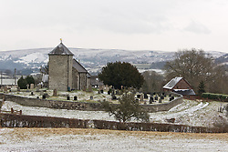 © Licensed to London News Pictures. 13/02/2021. Llanddewi'r Cwm, Powys, Wales, UK. St David's Church stands in a bitterly cold landscape as strong south east winds and snow hit Mid Wales with temperatures around minus 2.5 deg C and 'feels like' temperature around minus minus 5 deg C in Llanddewi'r Cwm, Powys, Wales, UK. Photo credit: Graham M. Lawrence/LNP
