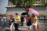 "Tourists at Qianmen (literally ""Front Gate"") is a gate in Beijing's historic city wall. The gate is situated to the south of Tiananmen Square and once guarded the southern entry into the Inner City. Although much of Beijing's city walls were demolished, Qianmen remains an important geographical marker of the city. The city's central north-south axis passes through Zhengyangmen's main gate. It was formerly named Lizhengmen meaning ""beautiful portal"". Zhengyangmen was first built in 1419 during the Ming Dynasty and once consisted of the gatehouse proper and an archery tower."