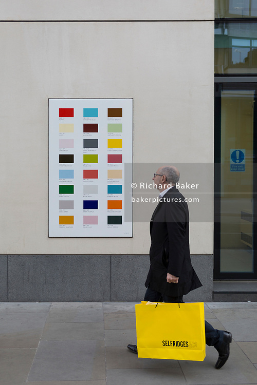 A male shopper carrying a yellow bag from Selfridges department store walks past a colour swatch on the wall of a central London business, on 22nd November 2017, in London England.