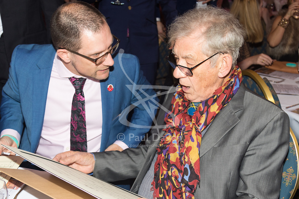 Old Town Hall, Stratford, London - 28 November 2015. Singers Marc Almond, Ronan Parke, Heather Peace and Asifa Lahore headline the Peter Tatchell Foundation's inaugural Equality Ball, a fundraiser for the foundation's LGBTI and human rights work, with guest of honour Sir Ian McKellen  joined by Michael Cashman. PICTURED:  Ed Fordham (L) with Sir Ian McKellen as he signs a musical score from Lord of The Rings, to be raffled.  //// FOR LICENCING CONTACT: paul@pauldaveycreative.co.uk TEL:+44 (0) 7966 016 296 or +44 (0) 20 8969 6875. ©2015 Paul R Davey. All rights reserved.