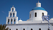 Low angle view of the Ekklisia (church) Agios Onoufrios with blue sky and Greek flag blowing in the wind, Oia, Santorini