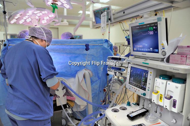Nederland, Nijmegen, 2-2-2018 Een operatie met behulp van scopen, laparoscopen in de operatieafdeling van het umc radboud. Het groene omgevingslicht zorgt voor een goed zicht op de beeldschermen waarop de ingreep gevolgd wordt. NIET GEBRUIKEN BIJ ARTIKELEN OVER FRAUDE OF FOUTEN IN DE ZORG. Foto: Flip Franssen