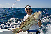Happy angler posing with jig caught Gag Grouper.