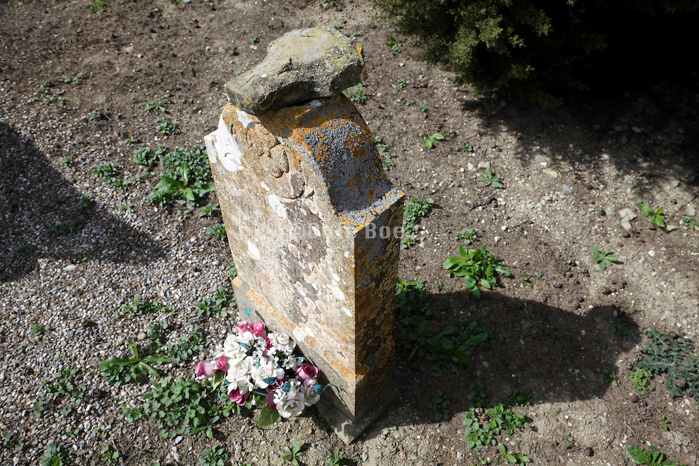headstone in graveyard with stone placed on top