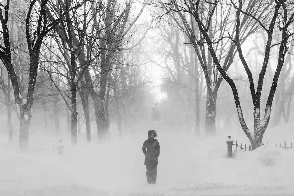 A pedestrian waiting at a crosswalk during a blast of frigid wind during Winter Storm Neptune in Boston.