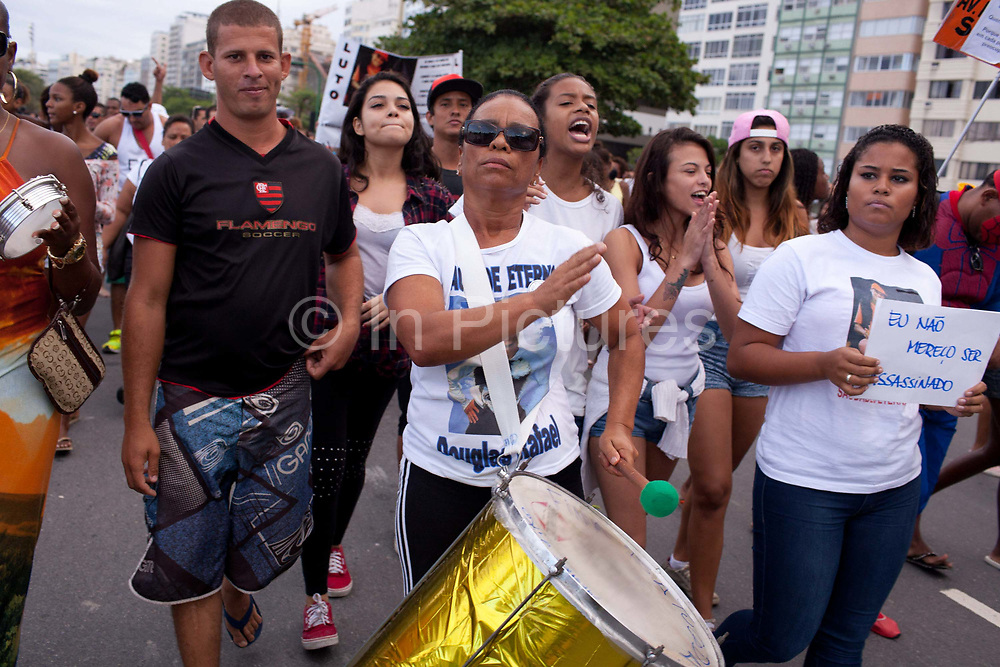 Protest in Copacabana, Rio de Janiero, in response to the mysterious death of professional dancer Douglas Rafael da Silva Pereira, allegedly at the hands of the Police. The favela Pavao-Pavaozinho that sits in between Copacabana and Ipanema. These protests saw a rare solidarity between the mostly middle class black bloc movement and members of the favela community. Here, Maria de Fatima da Silva, mother of Douglas drums and talks to the crowd.